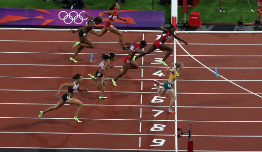 Australia's Sally Pearson (yellow) dips on the line to win gold ahead of United States's Dawn Harper (top)during the women's 100 metre hurdles final at the Olympic Stadium, London.